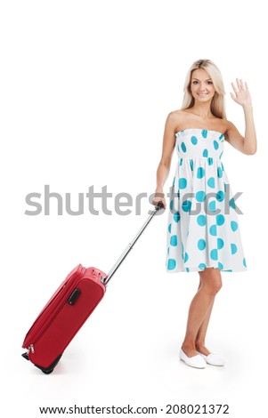 beautiful girl standing with luggage and smiling. Young girl waving hand on white background