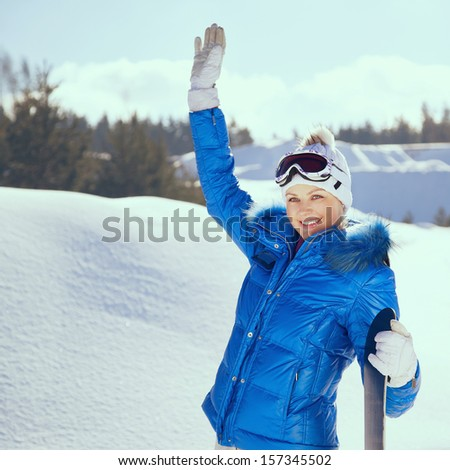 Beautiful girl standing with snowboard in her hand, smiling and waving. Sunny winter day, outdoors