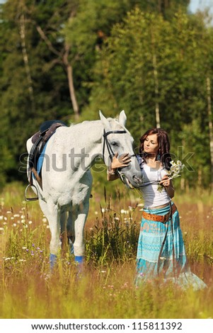 Beautiful girl stands on white horse on a summer meadow - stock photo
