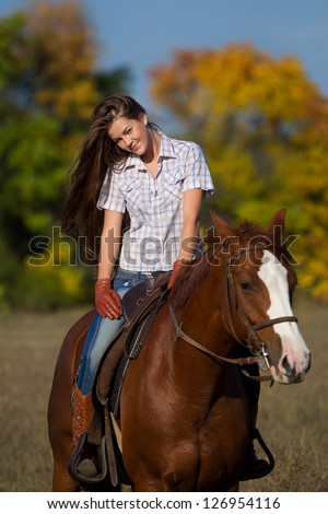 Beautiful girl  straddling a horse in garden - stock photo