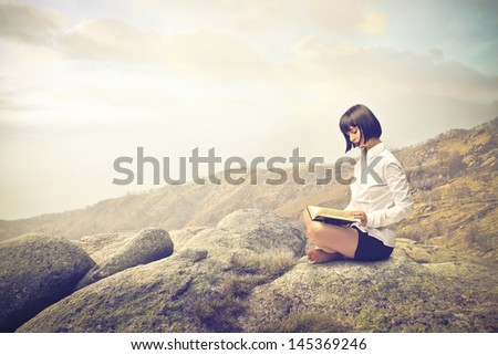 beautiful girl studying sitting on the rocks in the mountains