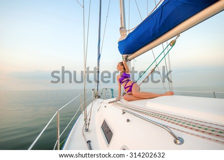 Beautiful girl sunbathing on the yacht. Rest on the yacht. Sailing yacht at the sea.