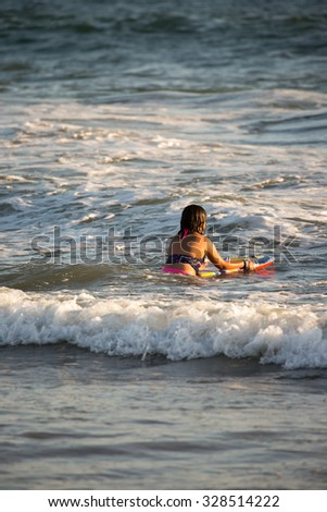 Beautiful girl Surfing a Wave on the ocean  - stock photo