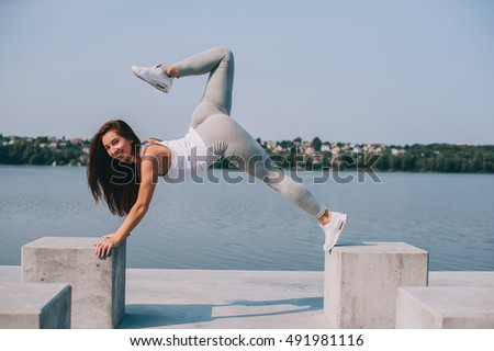 Beautiful girl takes exercises outdoors