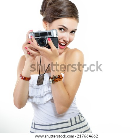 Beautiful girl takes her self picture with retro photo camera, over white. - stock photo