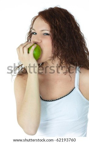 Beautiful girl taking a bite of a green apple, over a white background - stock photo
