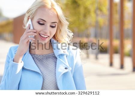 Beautiful girl talking on the phone on the autumn street - stock photo