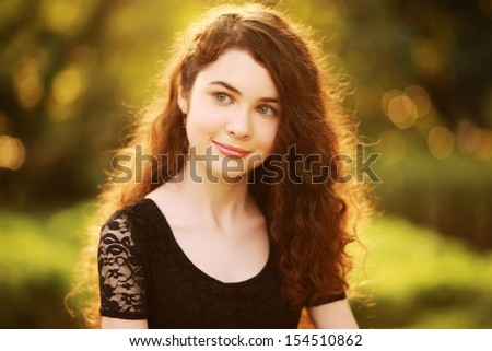 Beautiful girl thinking. Beauty portrait of a gorgeous young woman with fabulous hair, smiling & looking to left. Processed from RAW, detailed retouching.  - stock photo
