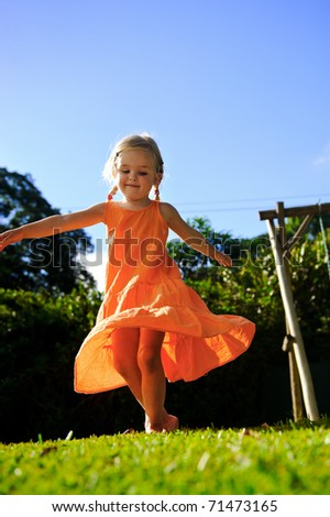 beautiful girl twirls in the sunset in her orange dress with blonde hair in pigtails - stock photo