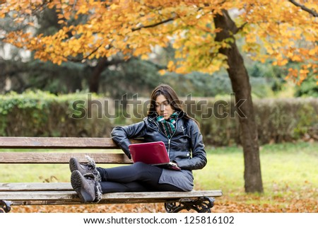 Beautiful girl using a laptop on a park bench - stock photo