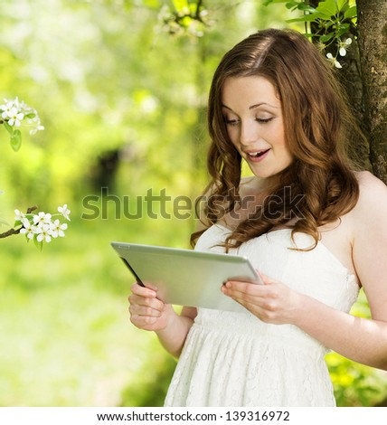 Beautiful girl using tablet in green park