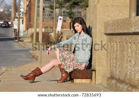 beautiful girl waiting for a ride at the side of a city road - stock photo