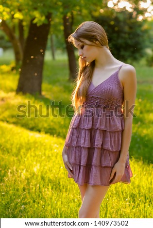 Beautiful girl walking in the forest on sunny summer day. - stock photo