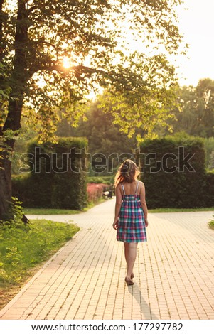 beautiful girl walking in the summer park on sunset