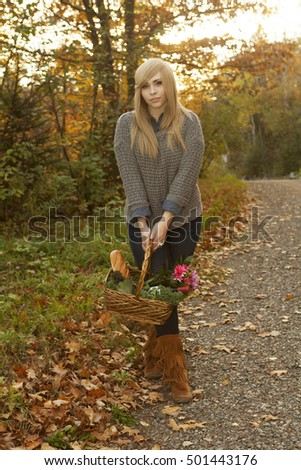 Beautiful girl walking outdoors in autumn with a basket from the farmers market.