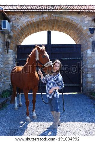 Beautiful girl walking with horse on gates background - stock photo