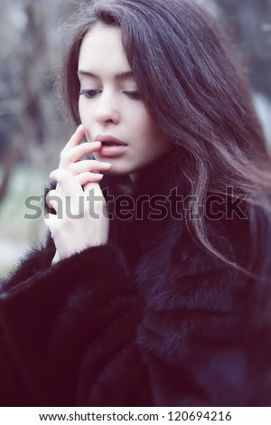 Beautiful girl warming his hands on the street. - stock photo