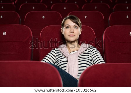 Beautiful girl watching a movie at the cinema - stock photo