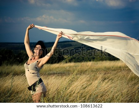 Beautiful girl waving white pareo in a summer field over blue sky - stock photo