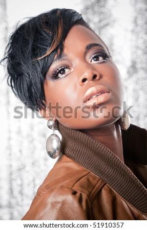 Beautiful girl wearing a leather jacket, studio portrait on shiny background - stock photo