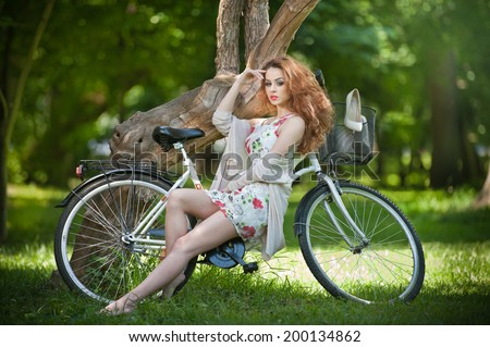 Beautiful girl wearing a nice short dress having fun in park with bicycle. Pretty red hair woman with romantic look posing sitting on her bike in a sunny day. Gorgeous curly redhead relaxing outdoor.  - stock photo