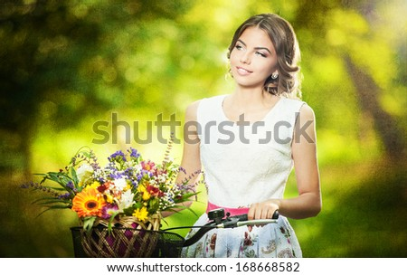Beautiful girl wearing a nice white dress having fun in park with bicycle carrying a beautiful basket full of flowers. Vintage scenery. Pretty blonde girl with retro look, bike and basket with flowers - stock photo