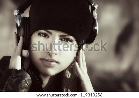 Beautiful girl wearing beanie hat with headphones listening to music - stock photo