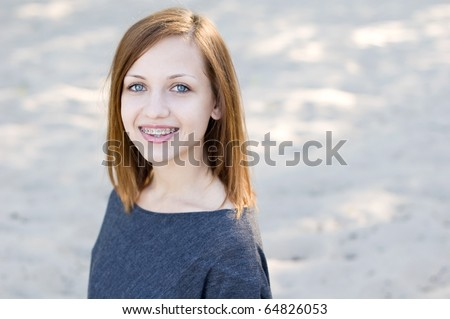 Beautiful girl wearing braces and smiling charmingly - stock photo