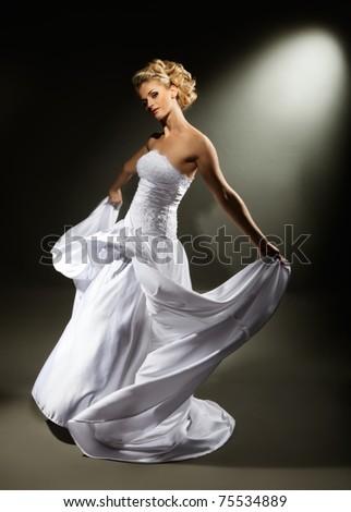 beautiful girl wearing luxurious wedding dress over studio background - stock photo