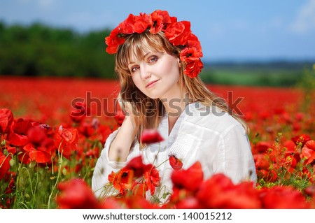 Beautiful girl wearing poppy headband standing in a poppy field - stock photo