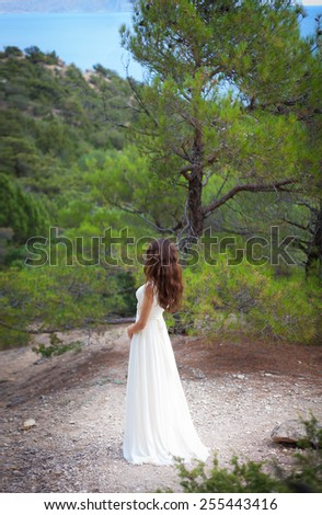 beautiful girl wearing white flowy dress in forest. Back view - stock photo