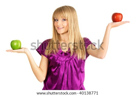 Beautiful girl weighing two fresh apples - stock photo