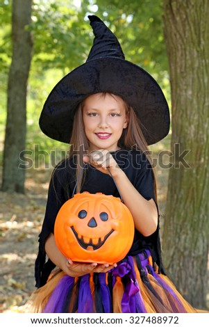 Beautiful girl witch and basket of candies in the park, outdoors