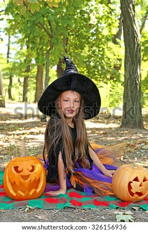 Beautiful girl witch with pumpkin in the park, outdoor