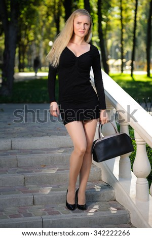 Beautiful girl with a bag in an autumn park - stock photo