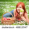 beautiful girl with a basket of apples on a meadow - stock photo