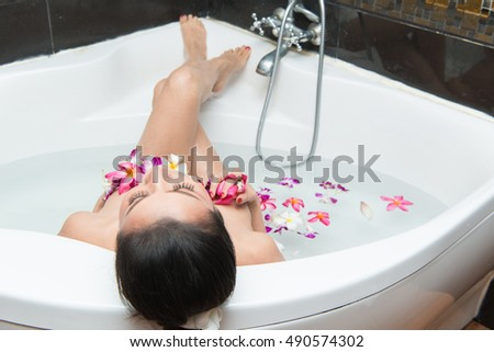 Beautiful girl with a beautiful flower in the bathtub Concept Spa  asia woman  in the spa salon. Beauty treatment concept