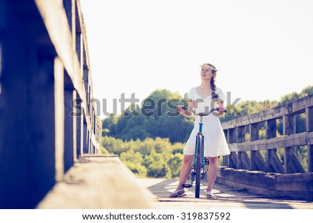 Beautiful girl with a bicycle on the bridge. - stock photo