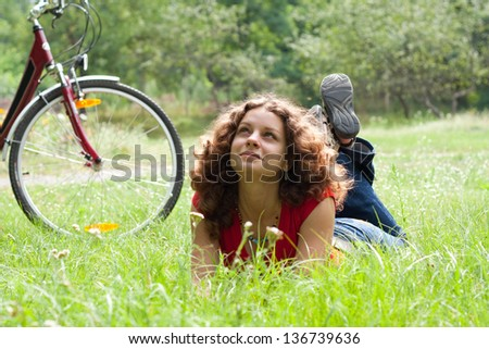 Beautiful girl with a bicycle  on the grass - stock photo