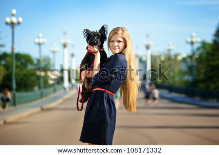 beautiful girl with a black dog on the background of the bridge in the park - stock photo