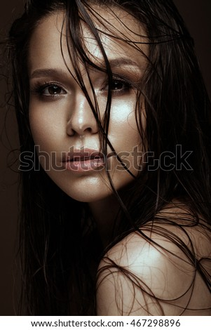 Beautiful girl with a bright make-up and wet hair and skin. Beauty face. Picture taken in the studio on a black background.
