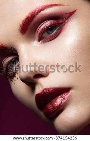 Beautiful girl with a bright red fashion makeup and crystals on the face. Close-up portrait.