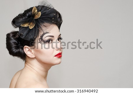 beautiful girl with a complicated hairstyle and make-up in profile on a gray background