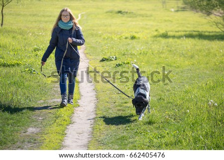 Beautiful girl with a dog on a walk
