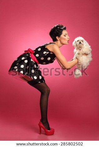 beautiful girl with a dog , vivid emotions, hairstyle and makeup style pin-pack, a good figure - stock photo