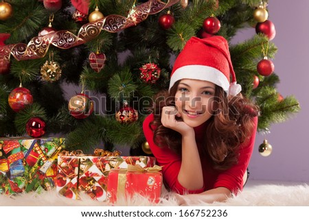 Beautiful girl with a gift near the Christmas tree - stock photo