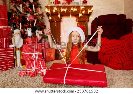 beautiful girl with a great gift near the Christmas tree. Red concept shooting - stock photo