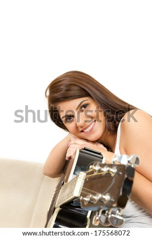 beautiful girl with a guitar smiling on the couch