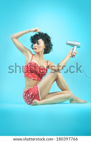 beautiful girl with a hairdryer in pajamas sitting in yoga pose - stock photo