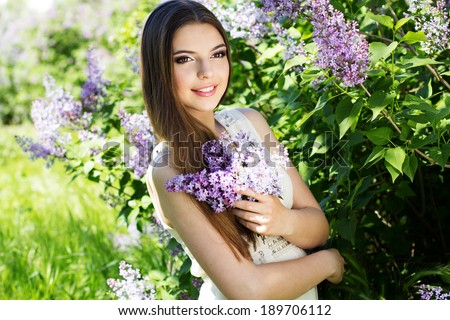 Beautiful girl with a lilac flowers - stock photo
